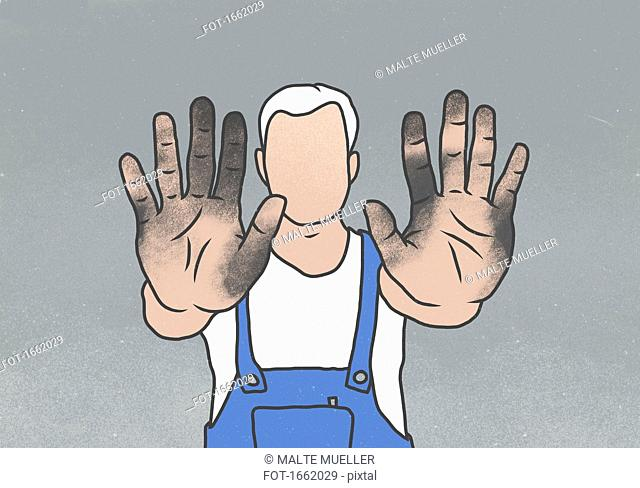 Manual worker showing messy hands while standing against gray background