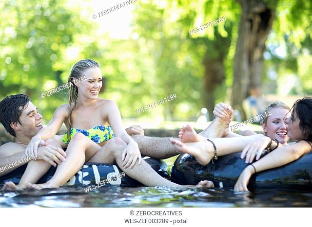 Friends on holiday having fun with inner tubes in a pool