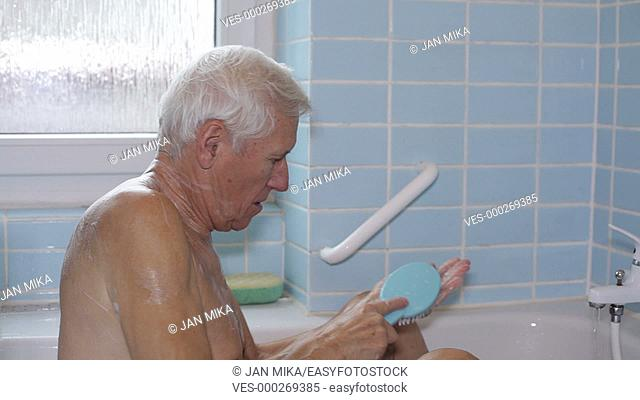Senior man washing his body with bath brush