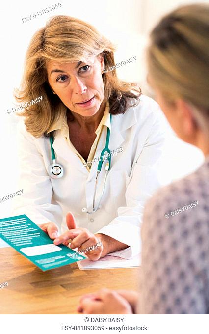 Doctor Discussing Leaflet With Female Patient