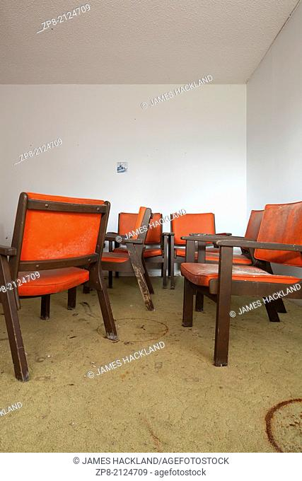 Vintage orange chairs gathering mold in an abandoned motel room in Ontario, Canada