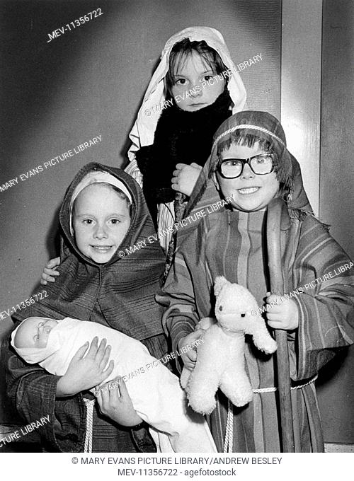 Three children taking part in a nativity play for Christmas, with a doll and a toy lamb