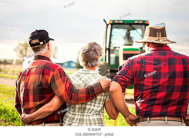 Rear view of farming family looking at tractor