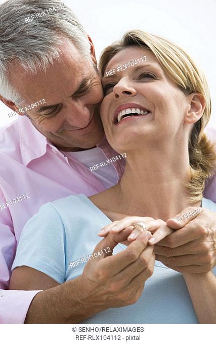 Mature couple, man putting diamond ring on woman's finger