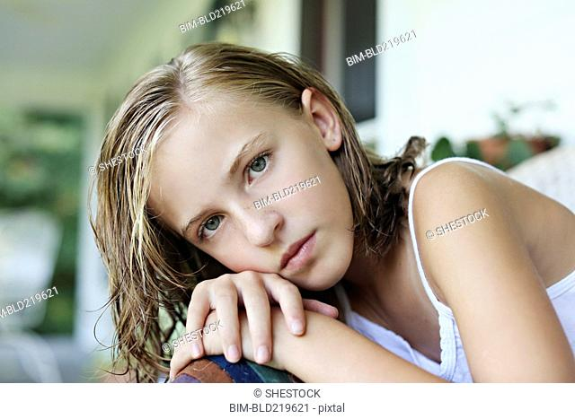 Close up of serious girl leaning in armchair