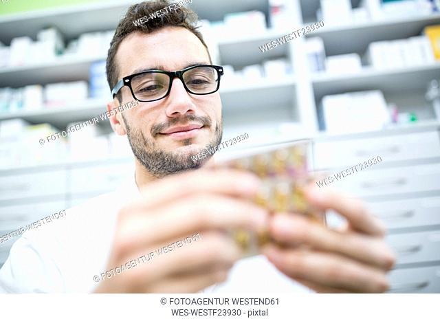 Smiling pharmacist holding tablet package in pharmacy