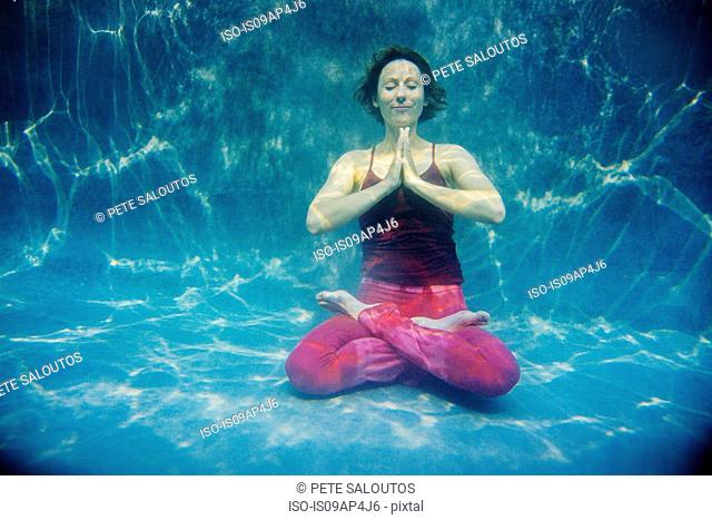 Mature woman wearing red yoga pants and vest, in yoga position, underwater view