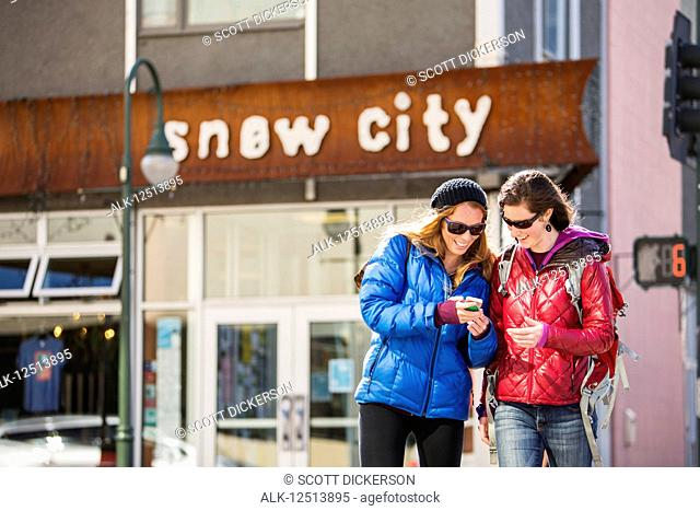Two young women look at a smart phone while outside a popular restaurant in downtown Anchorage, South-central Alaska; Anchorage, Alaska