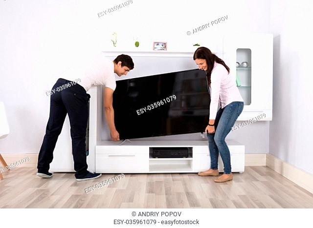 Young Couple Carrying Flat Television Screen In Their Modern House