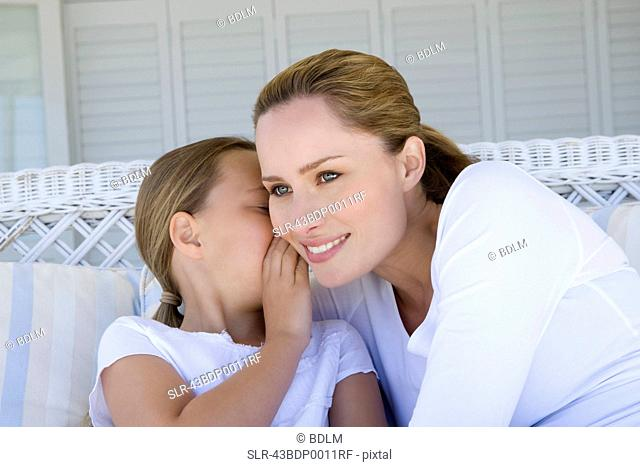 Girl whispering to smiling mother