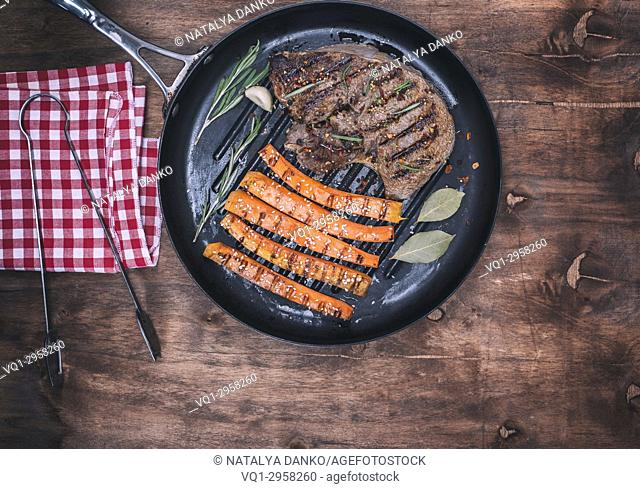fried beef stack and fried carrots on a round frying pan, brown wooden background, top view
