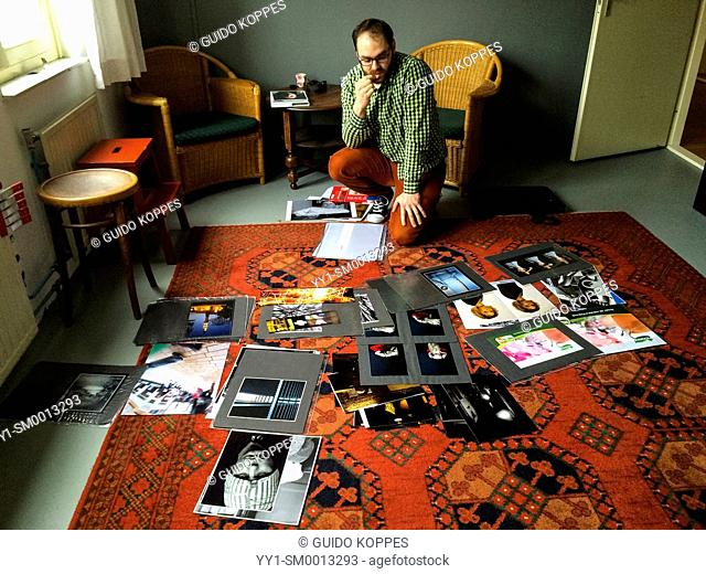 Tilburg, Netherlands. Young artist and photographer pondering his portfolio on the red carpet of Studio Tuinstraat