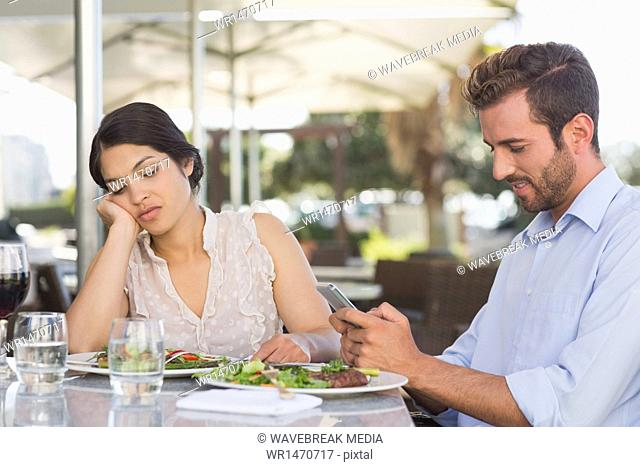 Bored woman being ignored by her date