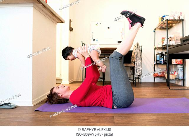 Mother doing leg raises with baby in arms