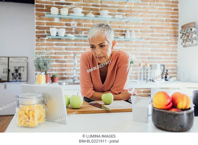 Older Caucasian woman cooking in kitchen