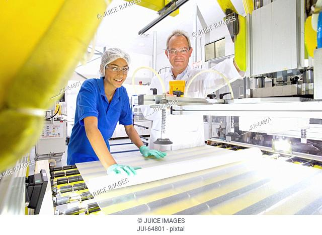 Engineer smiling at camera checking worker coating solar panel glass on production line on factory floor