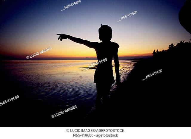 Woman pointing on beach at sunset. Visayas. Bohol. Philippines