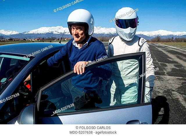Actor and TV host Claudio Bisio and racing driver The Stig getting into a car in the backstage of the TV show Top Gear Italia. Italy, 1st March 2016