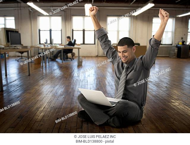 Hispanic businessman cheering at laptop in office