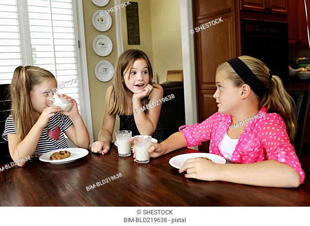 Sisters eating cookies with milk at table