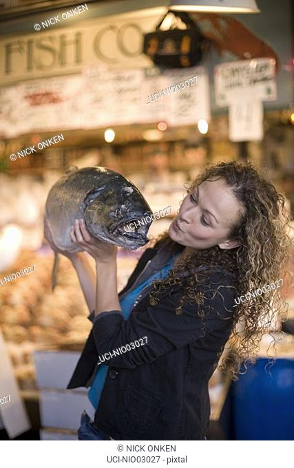 Young woman kissing a large fresh fish, Pike Place Market, Seattle, Washington