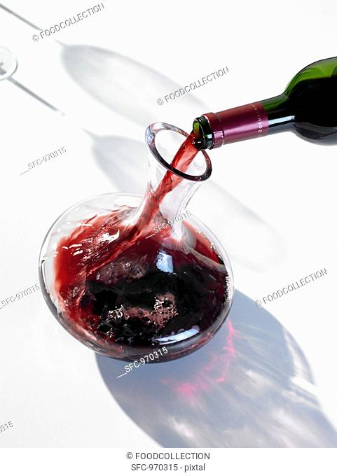 Pouring red wine into carafe