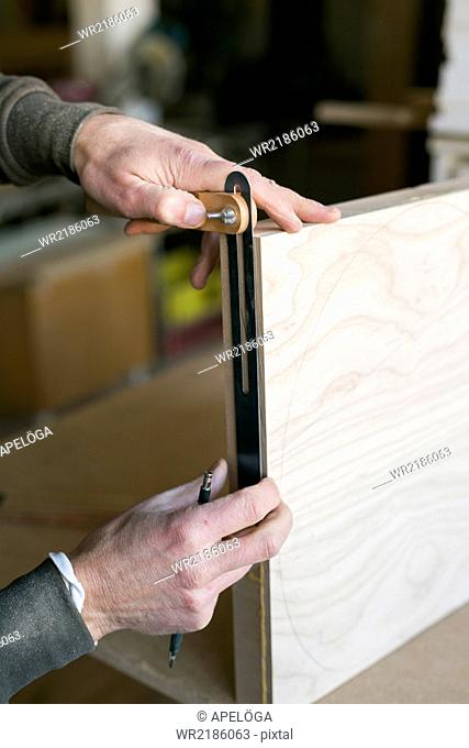 Close-up of carpenter's hands measuring wood in workshop