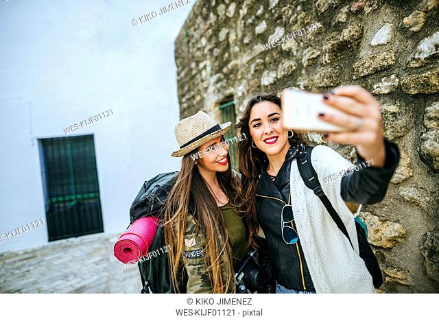 Two happy young women taking a selfie with a smart phone