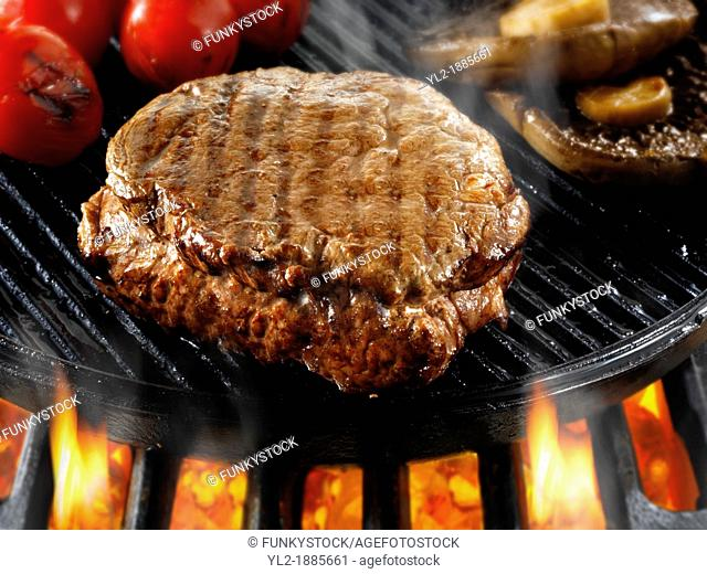 Beef fillet steaks & mushrooms being pan fried on a bbq Meat