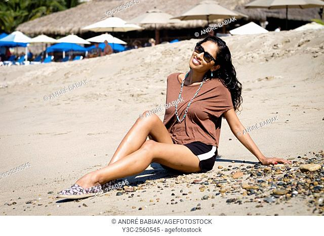 Hispanic woman in casual outfit enjoying to sit on the beach in Puerto Vallarta, Mexico