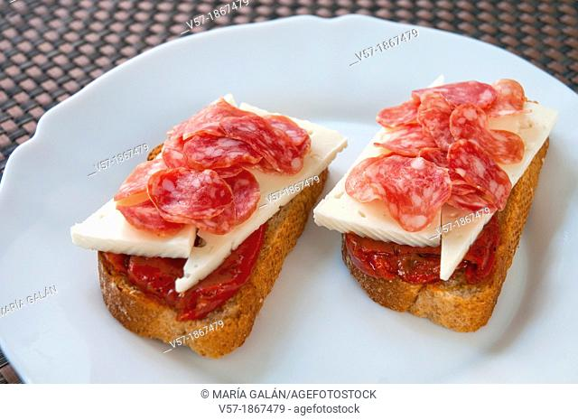 Spanish tapa: sliced fuet with cheese and red pepper on toast. Close view