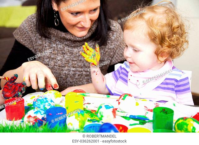 Mom and her daughter painting easter eggs