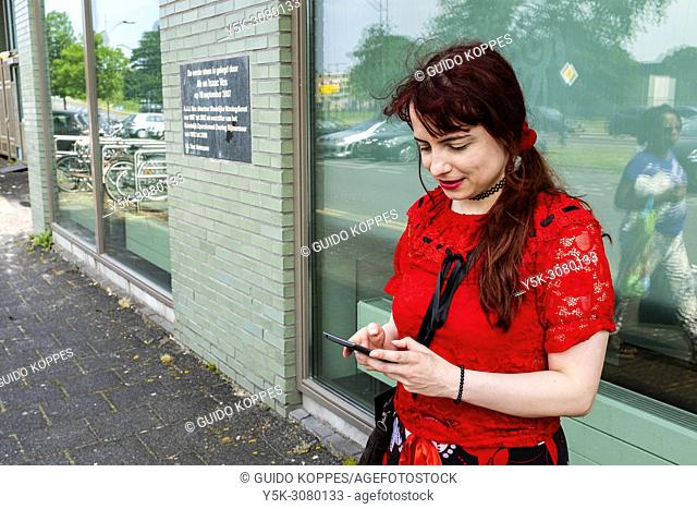 Amsterdam, Netherlands. Portrait of a young, redhaired woman using her smartphone for communication and navigation, in search of a nearby coffee place