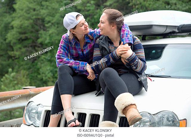Hikers chatting on bonnet of vehicle, Lake Blanco, Washington, USA