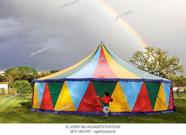 Boy running around a colored big top tent and a rainbow behind them