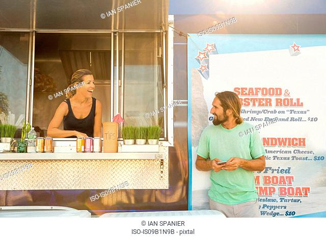 Man standing beside fast food trailer speaking to woman inside trailer