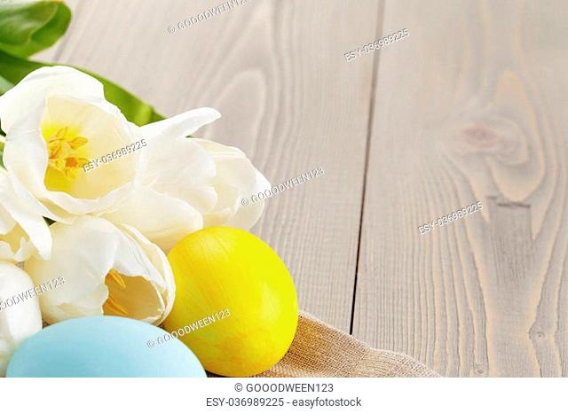 easter eggs and white tulips on wood table, copy space for text