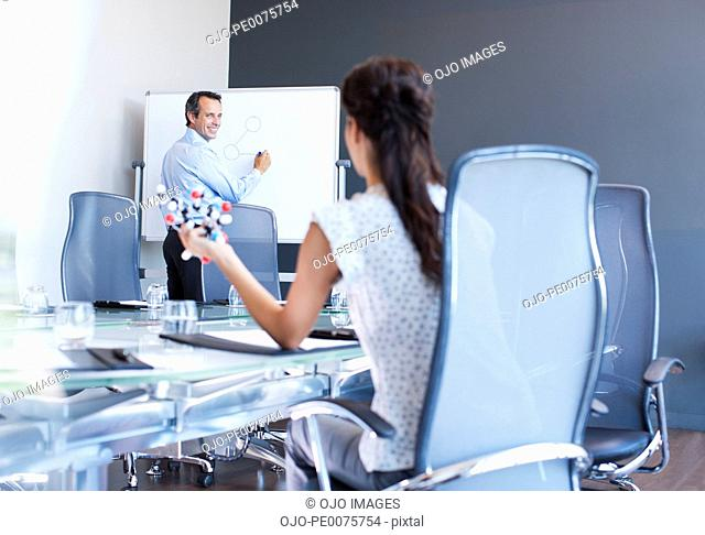 Business people working with molecule model in conference room