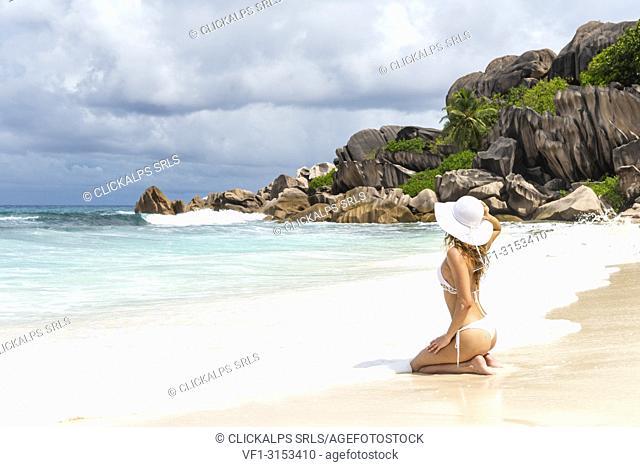 A beautiful woman enjoys the sun on the beach. La Digue island, Seychelles, Africa