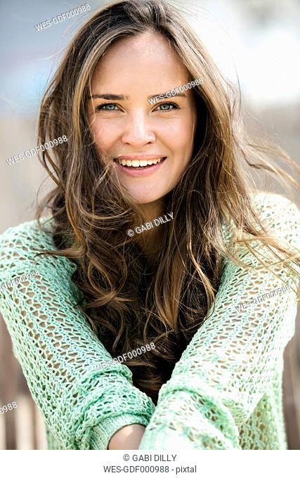 Portrait of smiling young woman with long brown hair