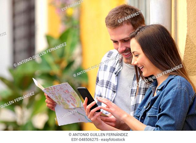 Two happy tourists checking map and smart phone on vacation in the street
