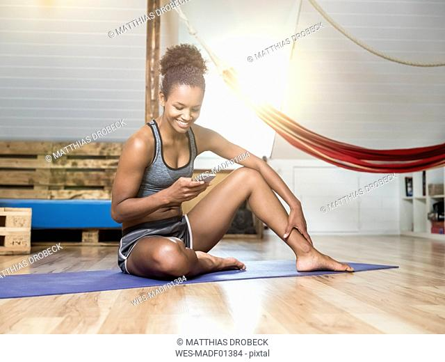 Smiling young woman sitting on yoga mat looking at cell phone