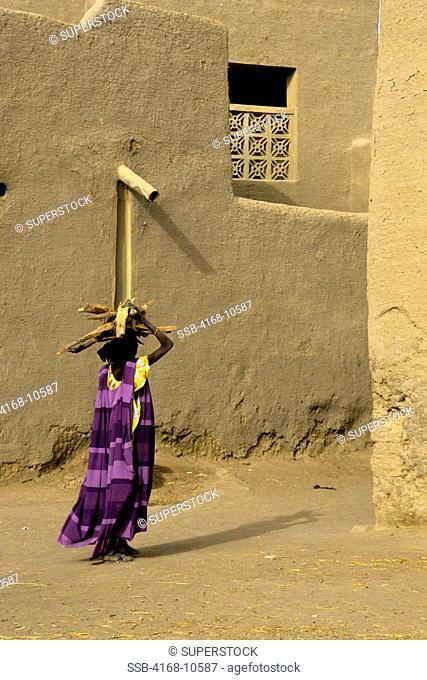 Mali, Djenne, Street Scene Woman Carrying Firewood On Back