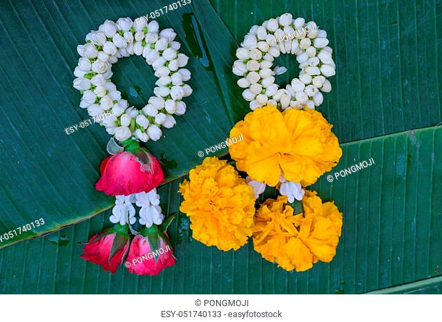 Beautiful garland jasmine and rose and calendula flower on green banana leaf