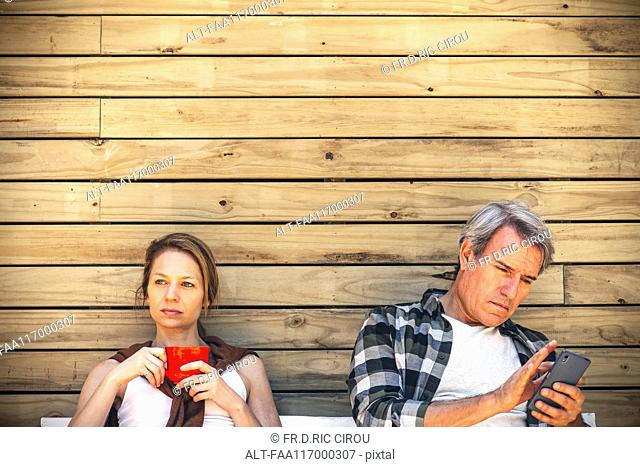 Woman holding coffee cup and man using smart phone in front of log cabin