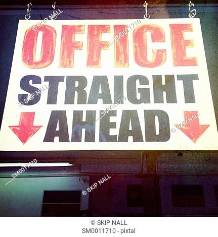 An overhead sign pointing the way to the office in an auto repair shop