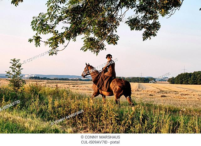 Woman riding horse in field