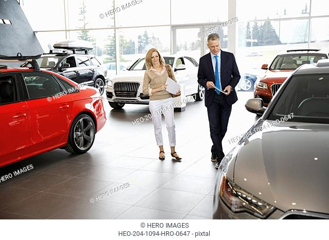Couple shopping in car dealership showroom