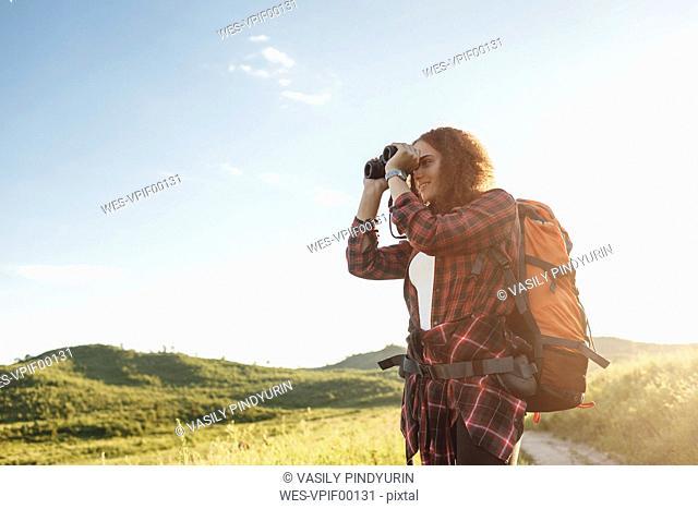 Teenage girl with backpack using binoculars in nature