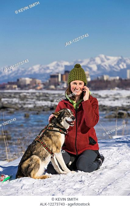Young woman with her Alaska Husky talks on a cell phone along the Tony Knowles Coastal Trail, Anchorage, Southcentral Alaska